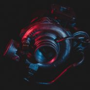 An old reconditioned car turbine, turbocharger, isolated on black with red and blue lighting.